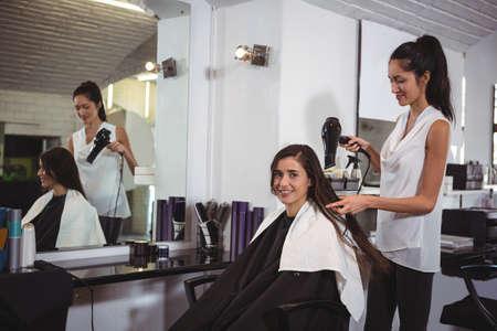 secador de pelo: Mujer que consigue el pelo se seca con secador de pelo en la peluquería