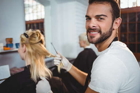 dyeing: Portrait of smiling male hairdresser dyeing hair of her client at a salon