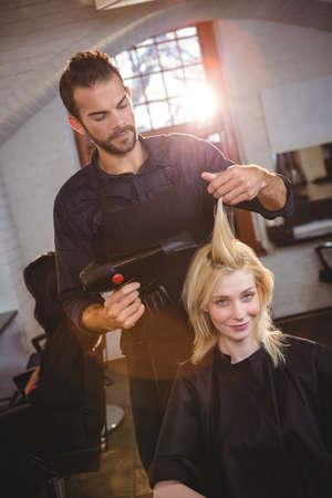 secador de pelo: Retrato de la sonrisa mujer obtener su cabello secado con secador de pelo en la peluquer�a