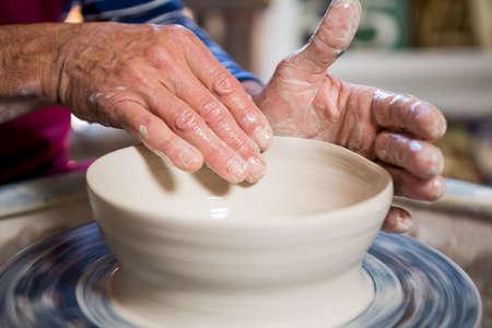 alfarero: Close-up of potter making pot in pottery workshop