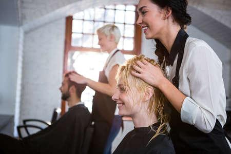 hair stylist: Smiling hair stylist massaging clients hair in salon