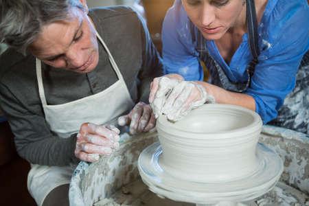 potter: Male potter assisting female potter in pottery workshop LANG_EVOIMAGES