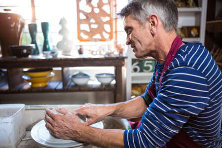potter: Male potter making pot in pottery workshop