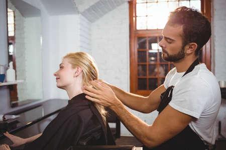 hair stylist: Handsome hair stylist styling woman hair in salon