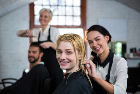 hairstylist: Portrait of smiling hairstylist combing client hair in salon