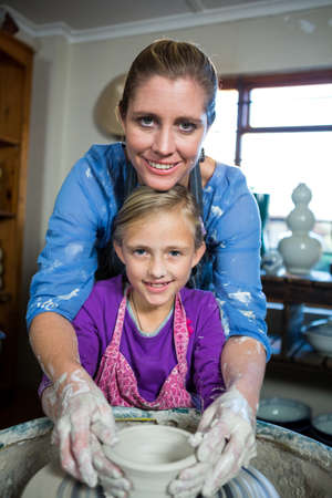 potter: Portrait of female potter assisting girl in pottery workshop LANG_EVOIMAGES
