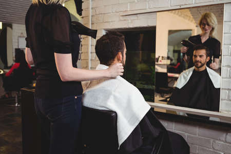 secador de pelo: Man getting his hair dried with hair dryer in salon LANG_EVOIMAGES