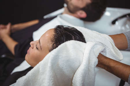 hair stylist: Hair stylist drying woman hair with towel in salon