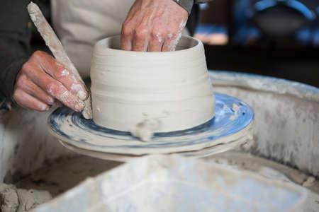 potter: Mid section of potter making pot in pottery workshop LANG_EVOIMAGES
