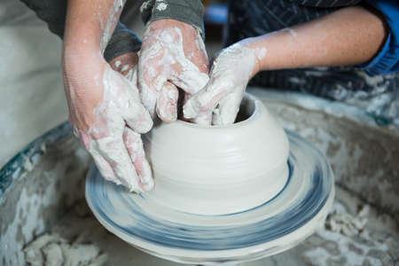 alfarero: Primer plano de alfarero ceramista masculina ayudar a la mujer en taller de cerámica