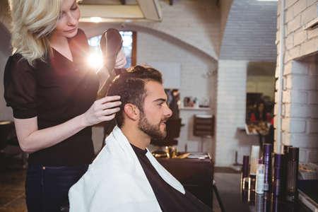 secador de pelo: Hombre que consigue el pelo se seca con secador de pelo en el salón