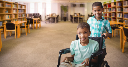 higher intelligence: Boy pushing friend on wheelchair against view of library