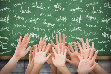 buzzwords: People raising hands in the air against blackboard on wall Stock Photo