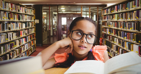 day dreaming: Young girl day dreaming by book at table against entrance of the college library