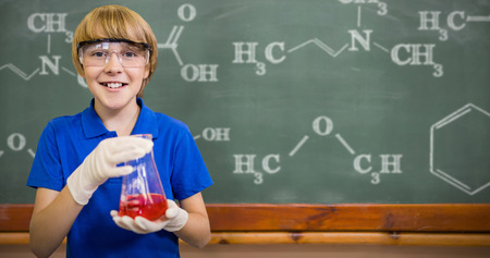 conical: Boy smiling while holding conical flask against blackboard