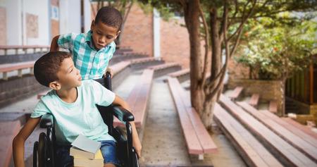 niño empujando: El muchacho empujando la silla de ruedas mientras amigo mirándolo contra parque