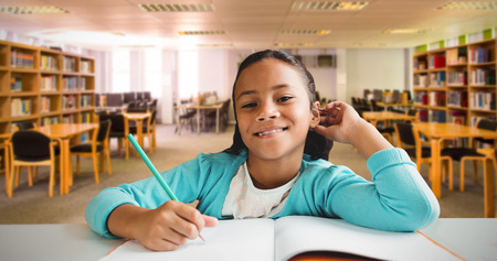 higher intelligence: Cute girl writing in a book against view of library