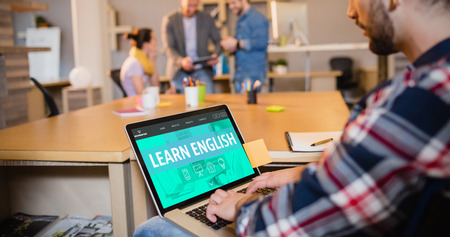 learn english: Learn english interface against graphic designer using laptop