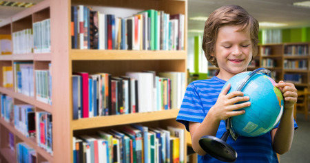 Happy boy holding globe while standing against  volumes of books on bookshelf in library  Volumes of books on bookshelf in library at the university Stock Photo