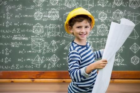 hard hat: Boy in hard hat holding a plan against blackboard