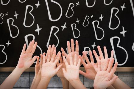 raising hands: People raising hands in the air against blackboard on wall Stock Photo
