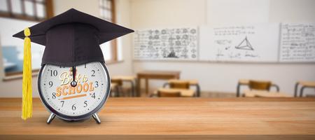 Mortar board on alarm clock  against empty classroom Stock Photo