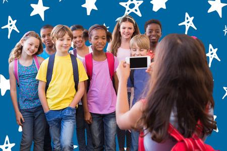 royal blue: Cute pupils using mobile phone  against royal blue