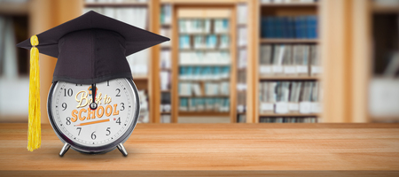 Mortar board on alarm clock  against library