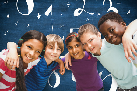 forming: Happy children forming huddle at park against blue chalkboard