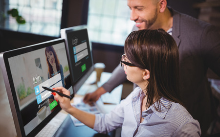 Log-in screen with redheaded woman against female photo editor discussing over computer with male colleague Stock Photo