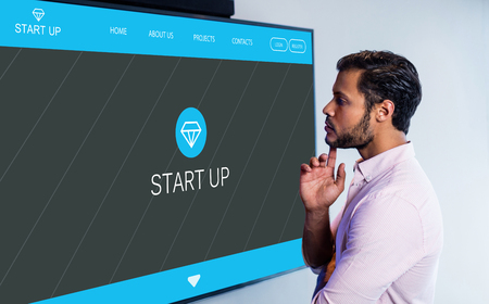 multiracial: Main web page on startup website against thoughtful man looking over whiteboard