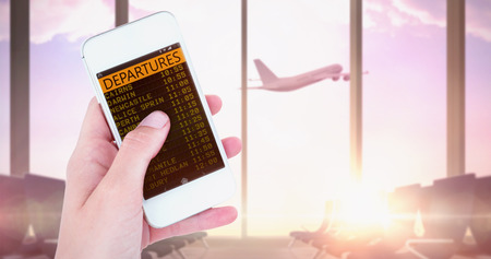Hand showing smartphone  against airplane flying past departures lounge window Stock Photo