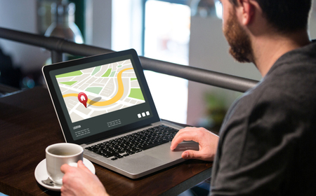 red  pointer: Navigation map with red pointer  against man holding coffee cup and using laptop