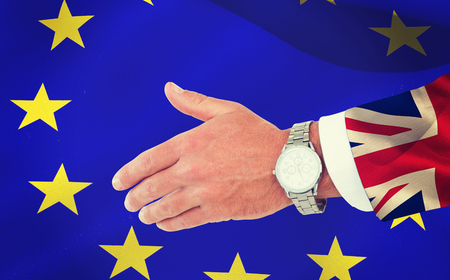 clenching: Businessman in suit clenching fists against digitally generated great britain national flag