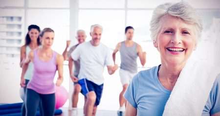 Portrait of a cheerful senior woman with people exercising in the background at fitness studio photo