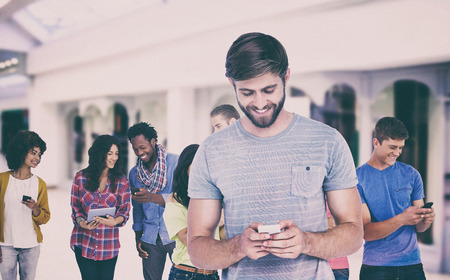 mal: Smiling young man using phone  against shopping mal Stock Photo