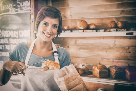 Pretty waitress picking up croissant at the coffee shop