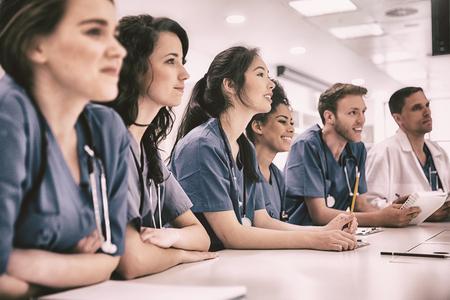 estudiantes medicina: Los estudiantes de medicina escucha sentado en el escritorio en la universidad