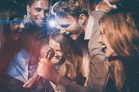 Gelukkige vrienden zingen karaoke samen in de nachtclub