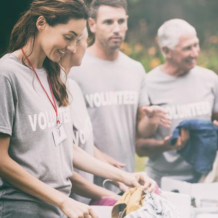 altruismo: Voluntario feliz que mira la caja de donación en un día soleado