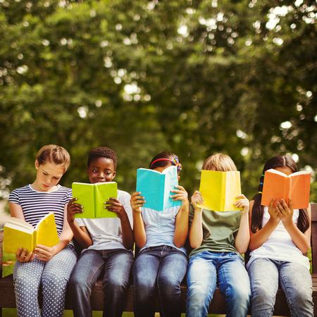 Children reading books at park against park
