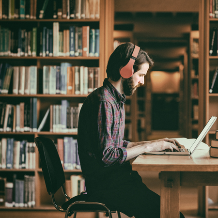 Hipster student studying in library at the university photo
