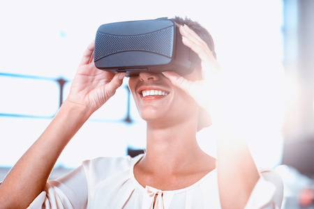 virtual office: Young woman using the virtual reality headset at office
