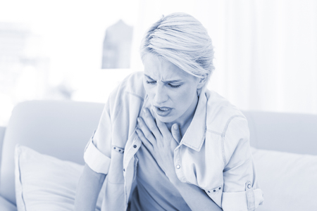 health fair: Pretty blonde woman having breath difficulties in the living room
