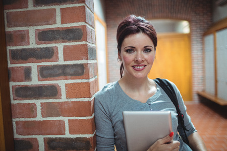 locker room: Portrait of mature student holding digital tablet in the locker room at college Stock Photo