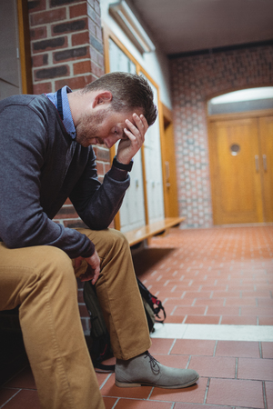 mature student: Stressed mature student sitting in locker room at college Stock Photo