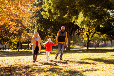middleaged: full length of family walking at park during autumn
