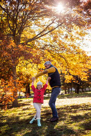 Full length of playful father with daughter at park during autumn