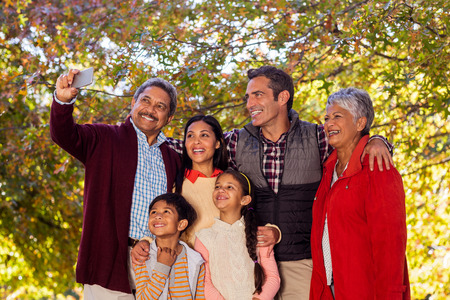 multigeneration: Cheerful multi-generation family taking selfie at park during autumn