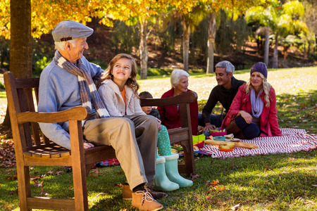 grand daughter: Family picnicking and the grandfather laughing with his grand daughter on a bench in a park